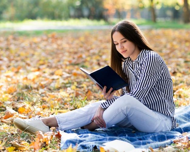 Bella donna che legge nel parco