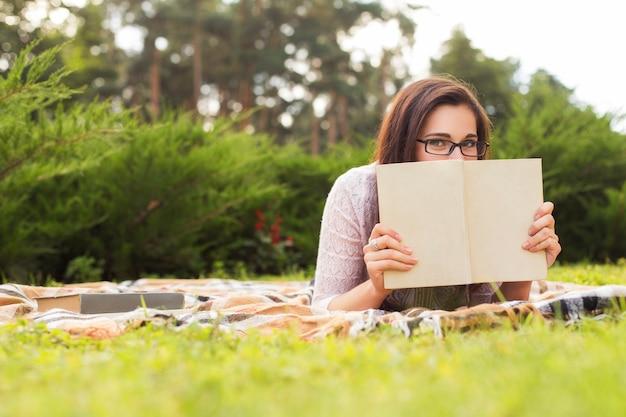Bella donna che legge un libro nel parco