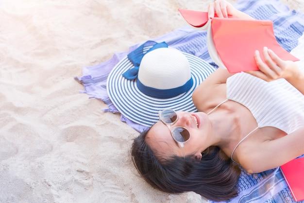 Bella donna che legge un libro sulla spiaggia tropicale. felicità vacanza rilassante.