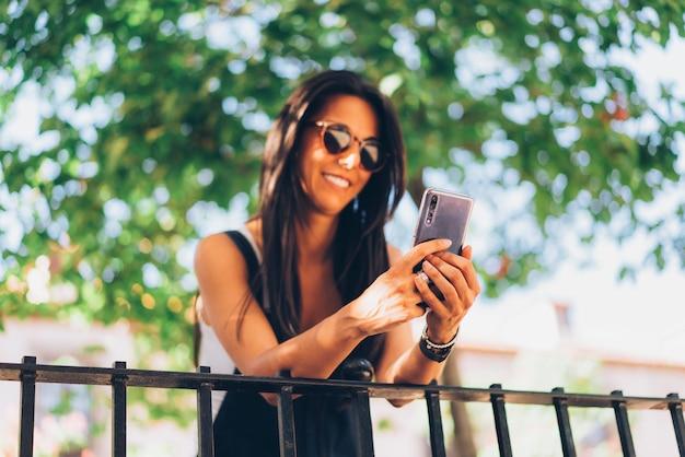 Bella donna che manda un sms su uno smartphone e che esamina cellula