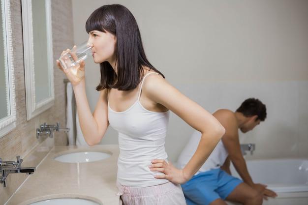 Bella donna che mangia bicchiere d'acqua con i denti di spazzolatura dell'uomo e della medicina