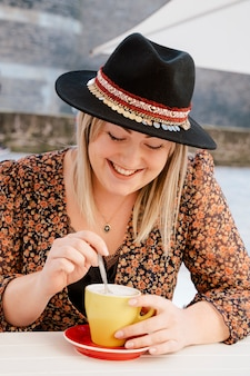 Bella donna che mangia caffè all'aperto ad un terrazzo soleggiato