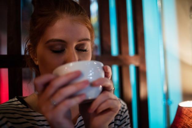 Bella donna che mangia caffè