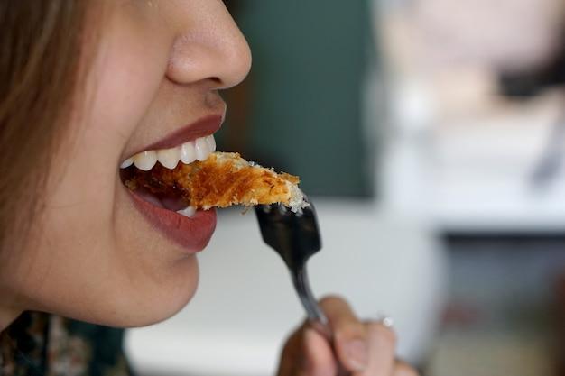 Bella donna che mangia croissant con forcella con volto di felicità