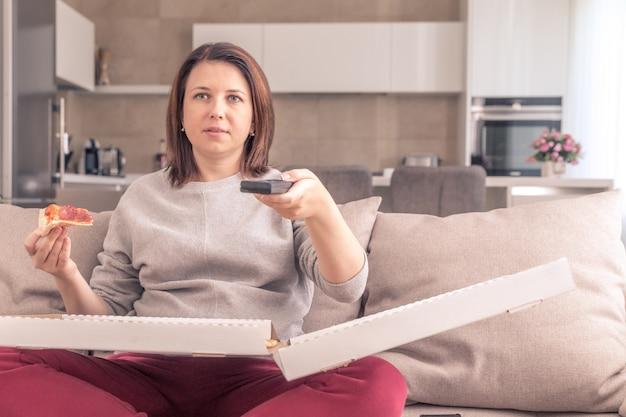 Bella donna che mangia pizza e che guarda la tv che tiene telecomando a casa, tono arancio