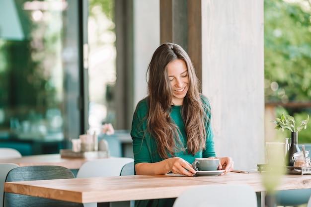 Bella donna che mangia prima colazione al caffè all'aperto. caffè bevente della giovane donna urbana felice