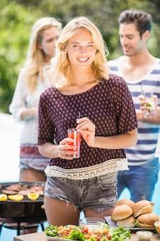 Bella donna che mangia succo alla festa all'aperto del barbecue