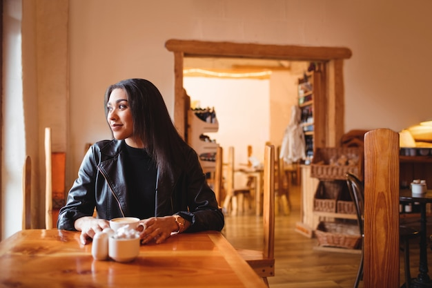 Bella donna che mangia una tazza di caffè nel café