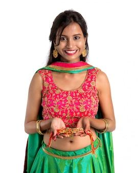 Bella donna che mostra rakhi in occasione di raksha bandhan su bianco. cravatta sorella rakhi come simbolo di intenso amore per suo fratello.