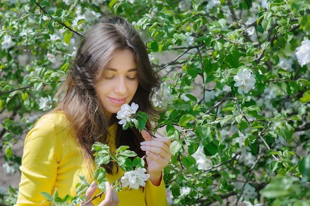 Bella donna che odora un giardino del fiore in primavera