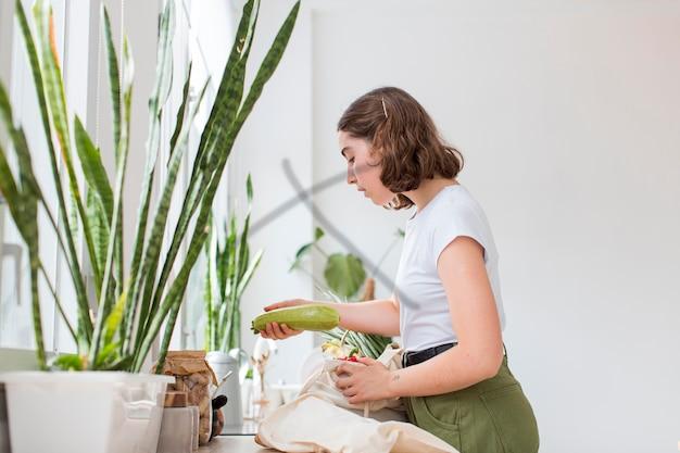 Bella donna che organizza generi alimentari biologici