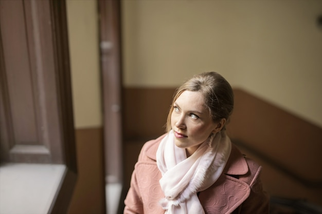 Bella donna che osserva da una finestra