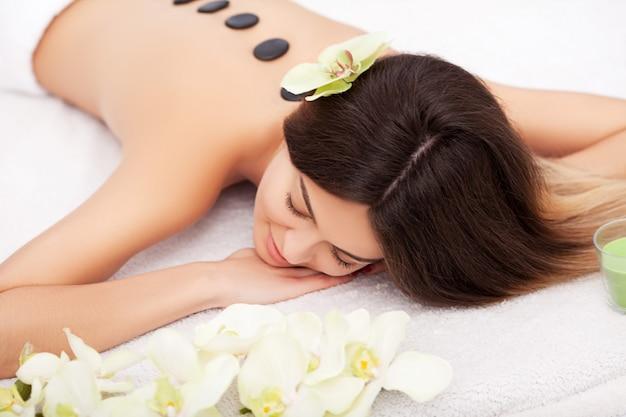 Bella donna che ottiene massaggio caldo delle pietre della stazione termale