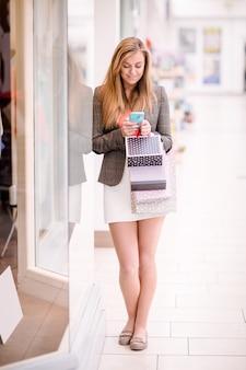 Bella donna che per mezzo del suo telefono mentre acquisto della finestra