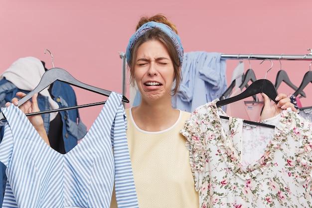 Bella donna che piange stando in guardaroba, con in mano due abiti alla moda di alto prezzo, senza soldi per comprarli. la femmina turbata e sorridente non riesce a trovare qualcosa di adatto a se stessa