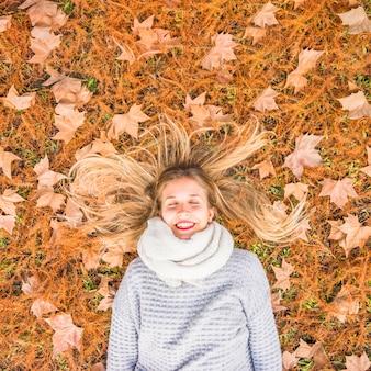 Bella donna che pone sulla terra di autunno