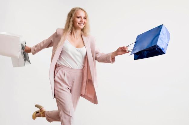 Bella donna che posa con i sacchetti della spesa