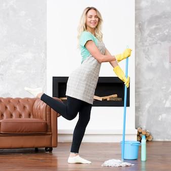 Bella donna che posa con la zazzera del pavimento che esamina macchina fotografica