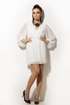 Bella donna che posa in abito bianco