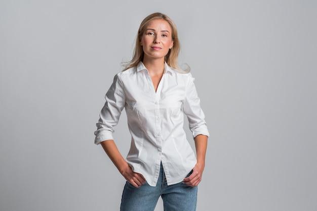 Bella donna che posa posa in jeans e camicia