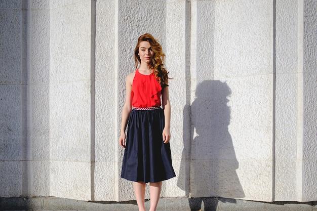 Bella donna che posa su un muro urbano