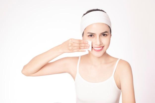 Bella donna che pulisce la sua faccia