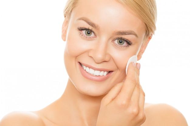 Bella donna che pulisce la sua pelle