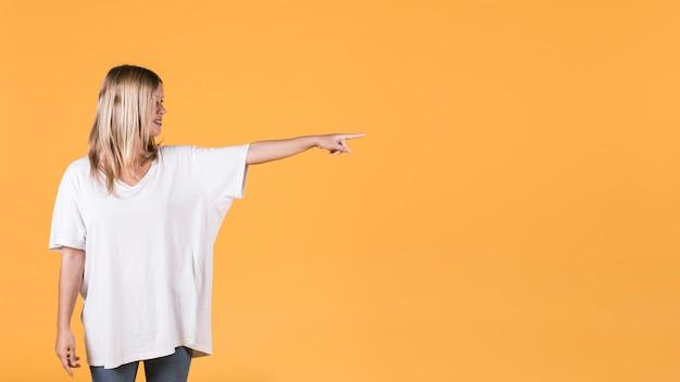Bella donna che punta al lato in piedi su sfondo giallo
