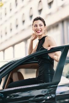 Bella donna che ride in piedi con uno sguardo felice nella porta di un'auto pronta a vincere il mondo