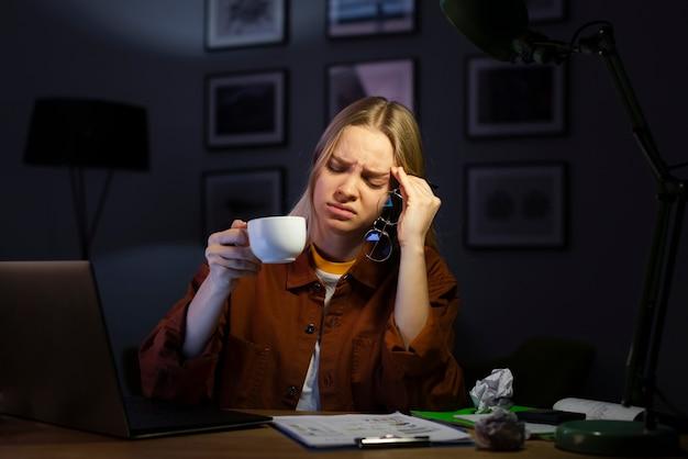 Bella donna che sembra stressata alla scrivania