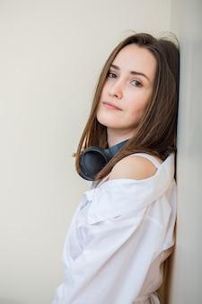 Bella donna che si appoggia sulla parete con le cuffie in camicia bianca