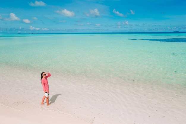 Bella donna che si distende alla spiaggia tropicale di sabbia bianca