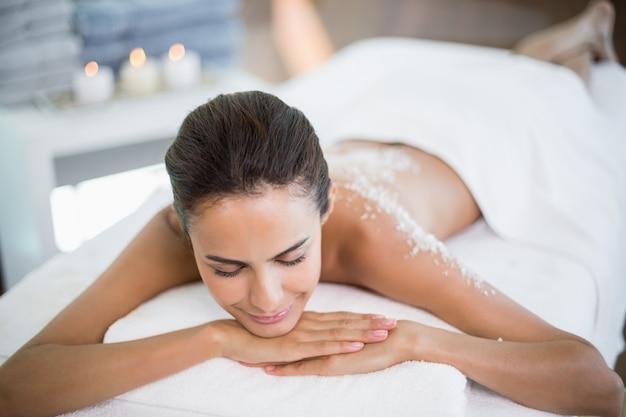 Bella donna che si distende sulla tabella di massaggio alla stazione termale
