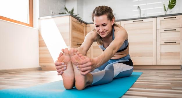 Bella donna che si estende sulla stuoia di yoga