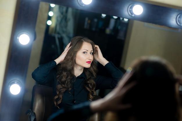 Bella donna che si guarda allo specchio