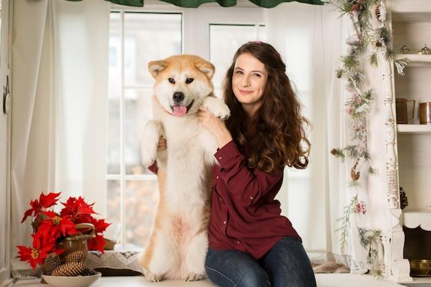 Bella donna che si siede retro comò dell'albero. abbracci, coccole con il suo cane akita inu.
