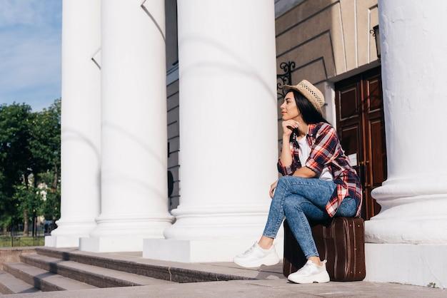 Bella donna che si siede sulla borsa dei bagagli che distoglie lo sguardo all'aperto