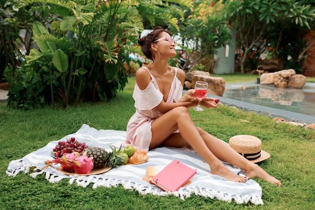 Bella donna che si siede sulla coperta, bevendo vino e godendo picnic estivo in giardino tropicale.