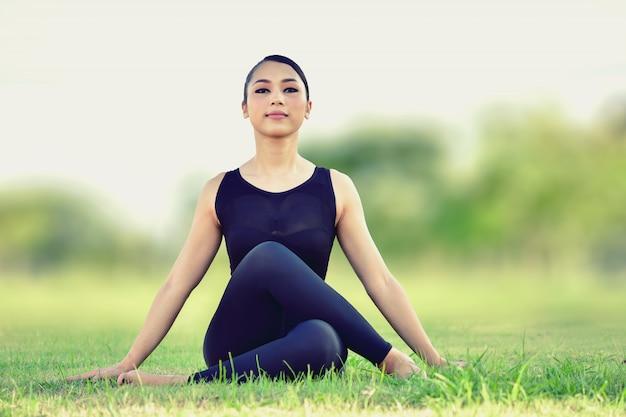 Bella donna che si siede sulle posizioni di yoga per un esercizio equilibrato del corpo.