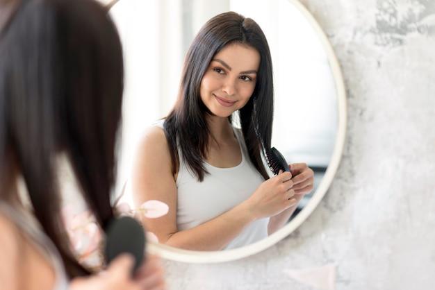 Bella donna che si sistema allo specchio