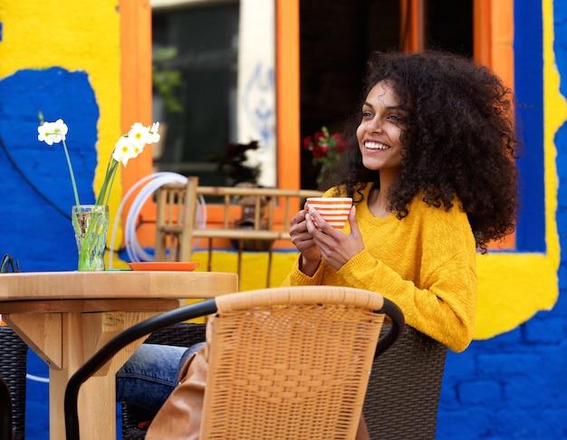 Bella donna che sorride con la tazza di caffè