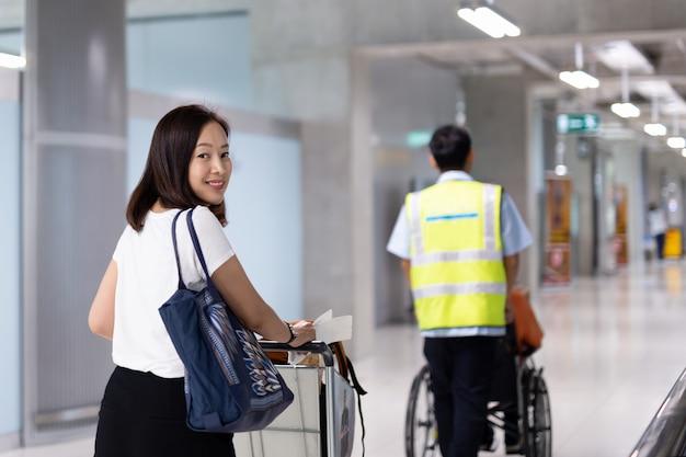 Bella donna che sorride sulla vacanza con il carrello dei bagagli nella costruzione dell'aeroporto.