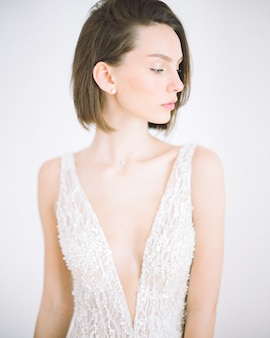 Bella donna che sta e che guarda in vestito bianco lungo nella sala con bianco