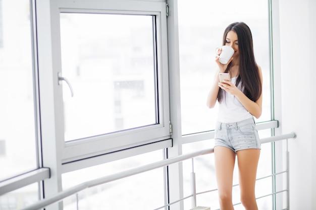 Bella donna che sta vicino alle finestre