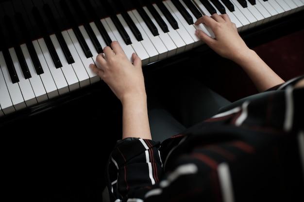 Bella donna che suona il pianoforte, impara a suonare il piano.
