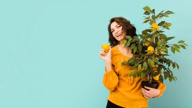 Bella donna che tiene un albero con lo spazio della copia