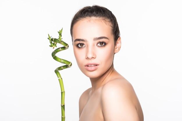 Bella donna che tiene un bastone di bambù su una parete bianca