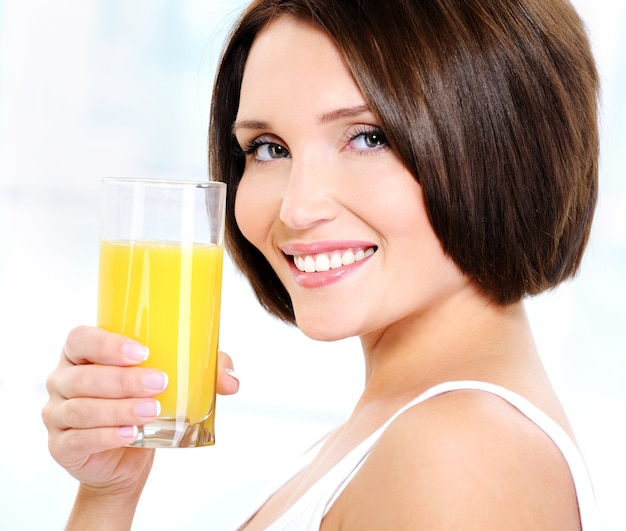 Bella donna che tiene un bicchiere di succo d'arancia