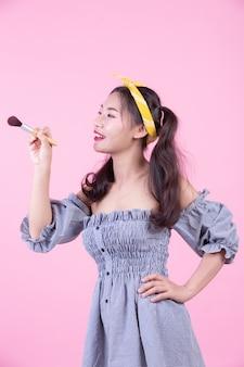 Bella donna che tiene un pennello, spazzolato su uno sfondo rosa.
