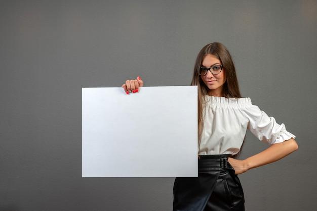 Bella donna che tiene un tabellone per le affissioni in bianco
